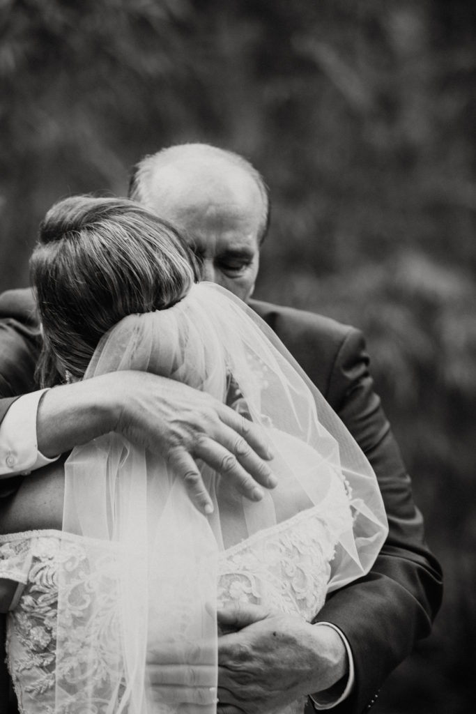 Father of the bride hugging his daughter.