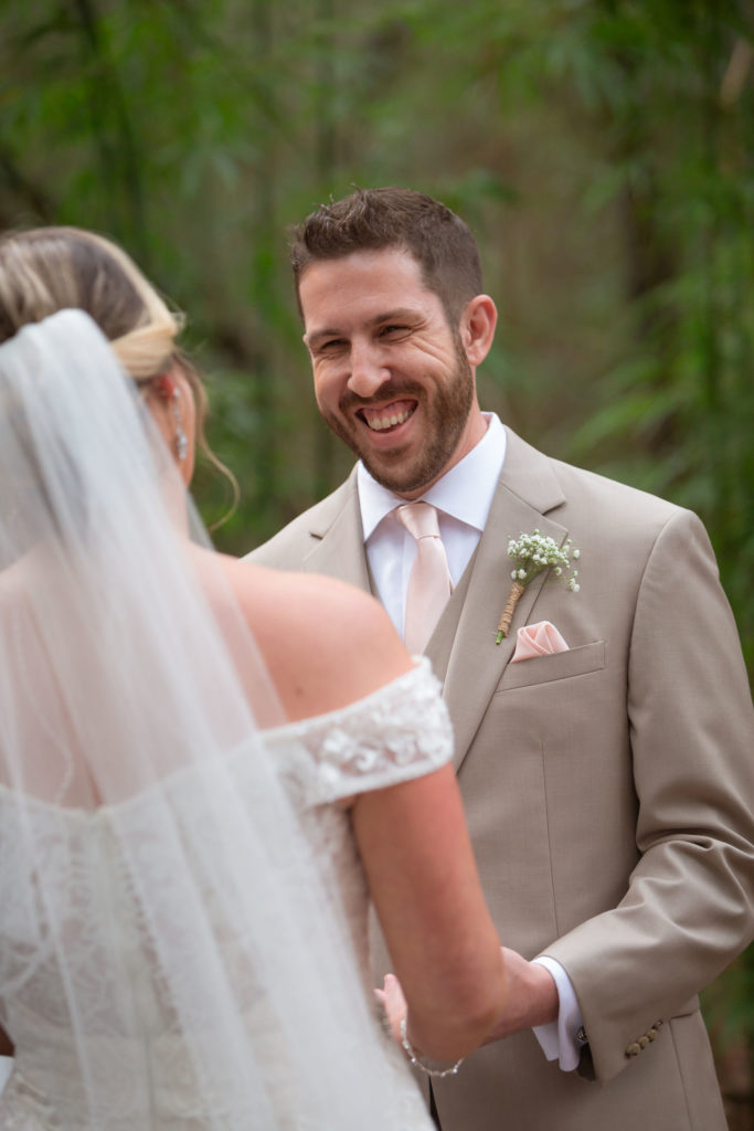The groom smiling at his bride during the ceremony.