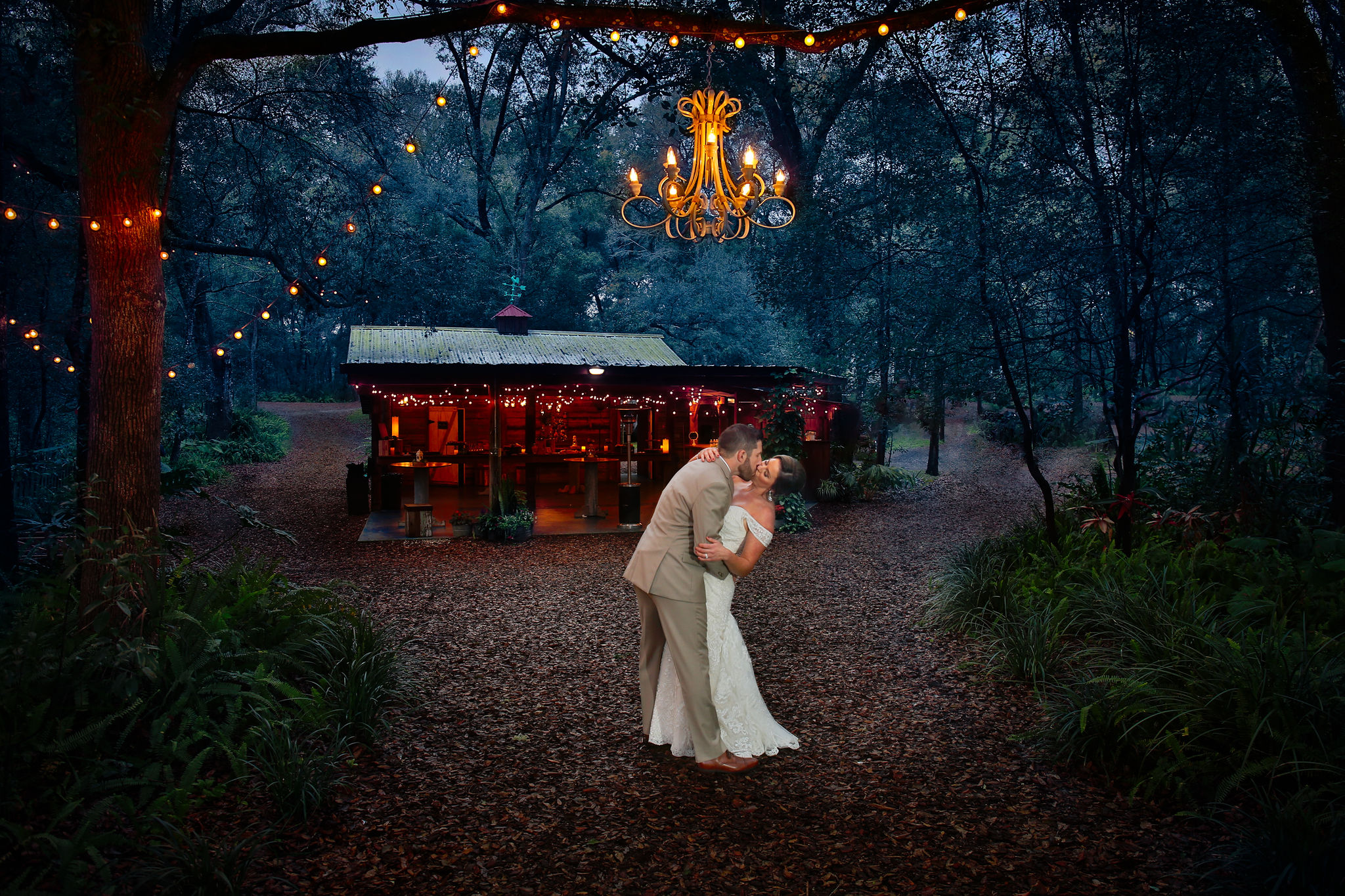Bride and groom kissing under the chandelier at Bridle Oaks.